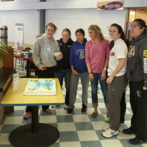 Surprised by cake members of the Alaska Nanooks women's basketball team posed for Lola TIlly's staff to take a picture. Photo by Fred Monrean Jr. Extreme Alaska