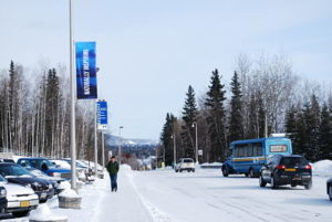 "A student walks under one of the new ""Naturally Inspiring"" banners on Yukon Dr."