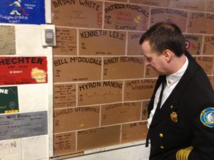 """Chief Douglas Schrage points out names on the UFD station house """"Wall of Fame"""".  -Photo by Micheal Ives, Extreme Alaska"""