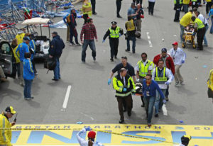 Medical workers wheel the injured across the finish line during the 2013 Boston Marathon following an explosion in Boston, Monday, April 15, 2013. Two explosions shattered the euphoria of the Boston Marathon finish line on Monday, sending authorities out on the course to carry off the injured while the stragglers were rerouted away from the smoking site of the blasts. AP Photo by Charles Krupa