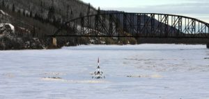 The Nenana Ice Classic tripod sits on the frozen Tanana River.  The Parks Highway/Mears Memorial Bridge provides background in Nenana, Alaska.
