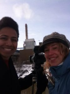 Teri and Ashleigh getting footage of a power plant on a steep riverbank.