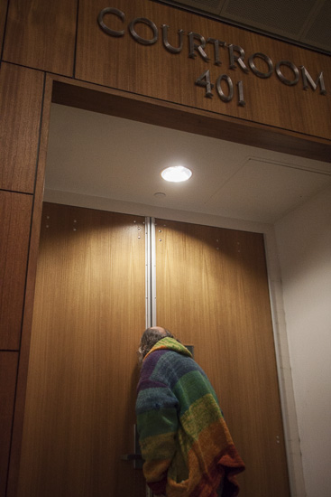 Image of Rev. Scott Fisher peeking through crack in courthouse door.