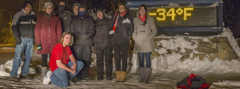 image of Extreme Alaska staff assembled at 34 below digital temp sign